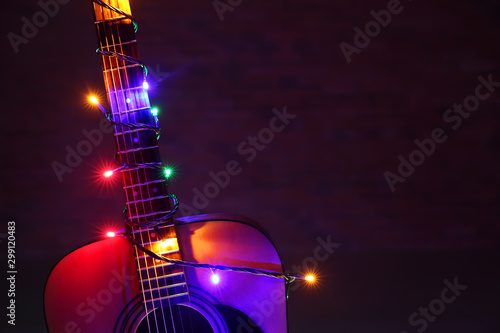 Fotografia Acoustic guitar with Christmas lights against dark background