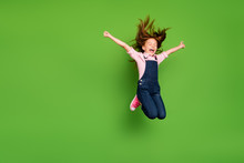 Full Length Photo Of Cheerful Pretty Little Schoolchild Jumping High Rejoicing Summer Holidays Hair Flying Wear Casual Denim Overall Pink Shirt Isolated Green Background