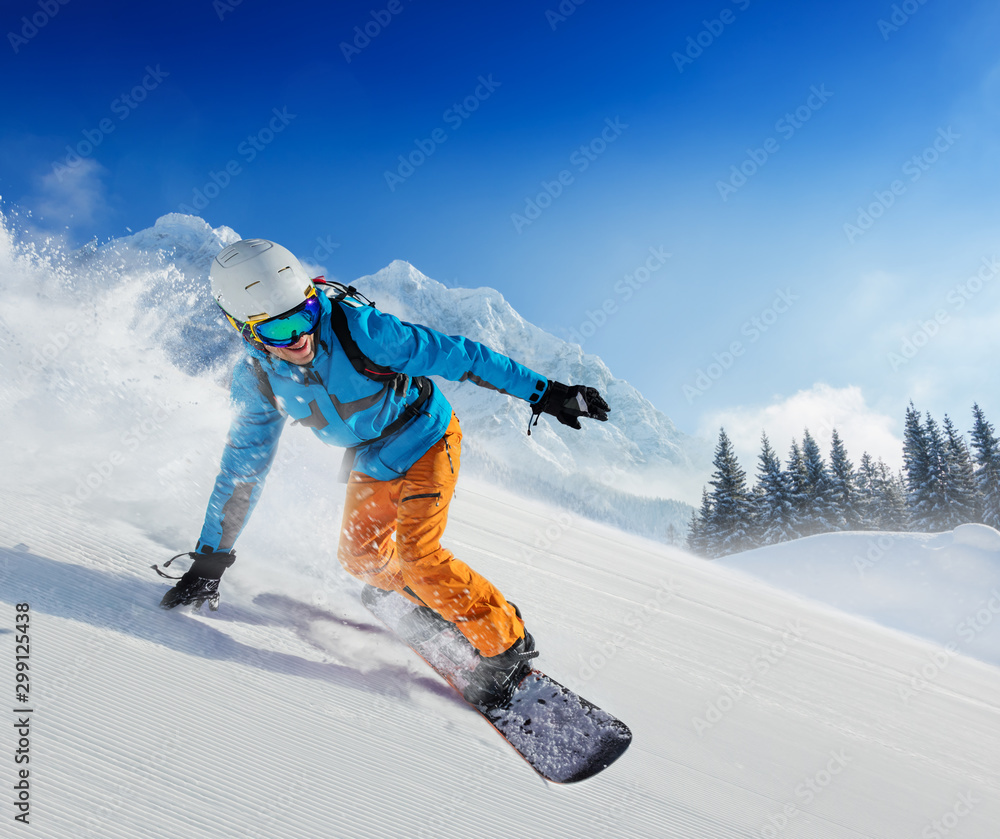 Fototapety, obrazy: Young man snowboarder running down the slope in Alpine mountains