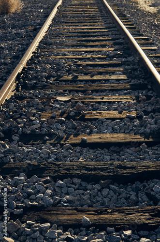 tor kolejowy z drewnianymi podkładami ze złotym światłem zachodzącego słońca, które zaznacza tekstury