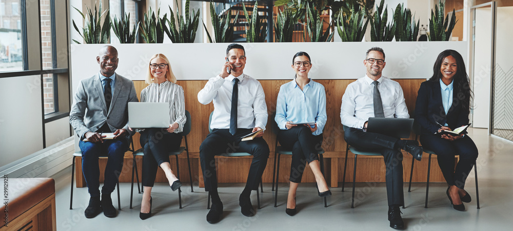 Fototapeta Smiling businesspeople sitting together in an office reception