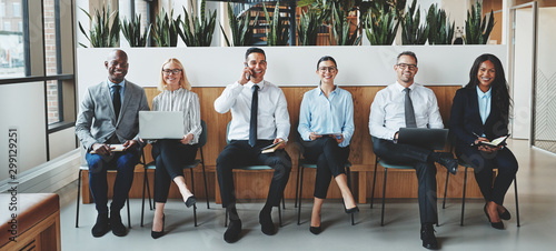 Smiling businesspeople sitting together in an office reception Canvas Print