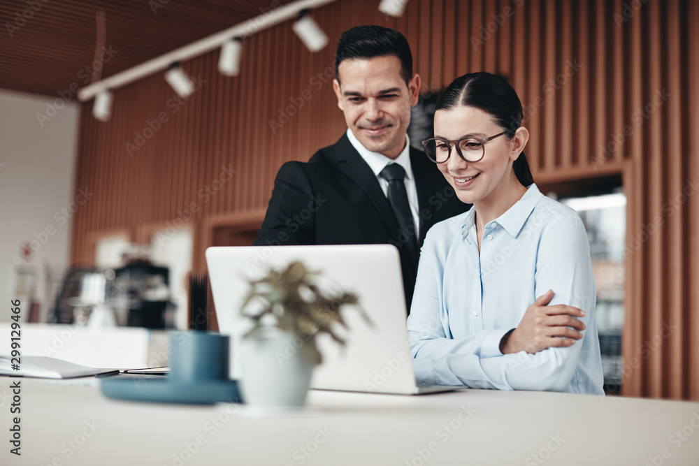 Fototapeta Smiling businesspeople standing in an office working on a laptop