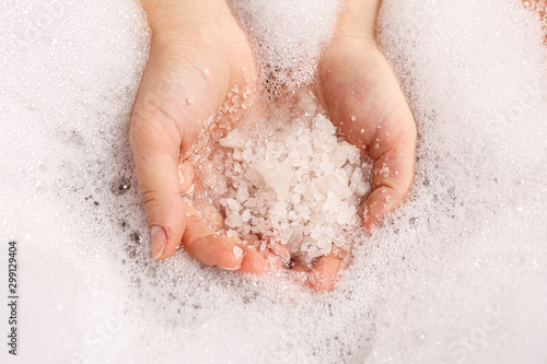Vászonkép white bath salt in a female hand dissolves in water