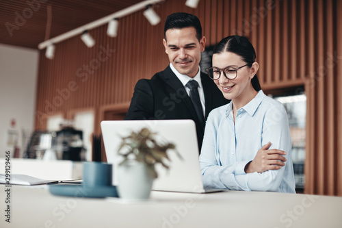 Fototapeta Smiling businesspeople standing in an office working on a laptop obraz