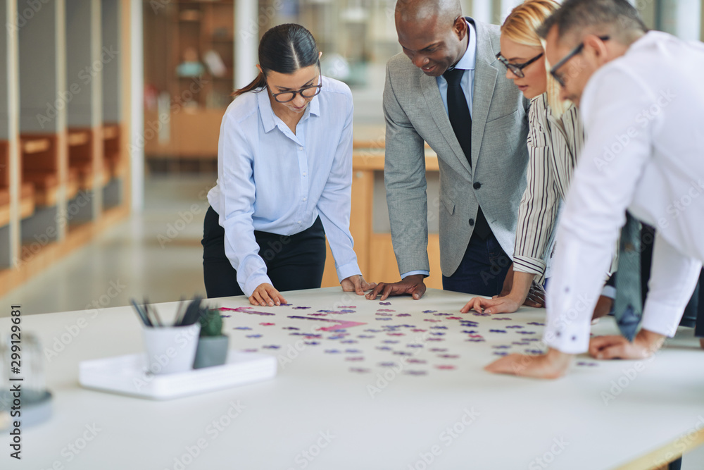 Fototapeta Diverse businesspeople solving a jigsaw puzzle together in an of