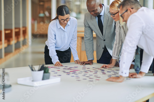 Diverse businesspeople solving a jigsaw puzzle together in an of