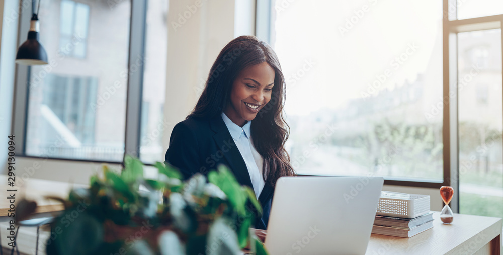 Fototapeta Smiling African American businesswoman using a laptop at her des