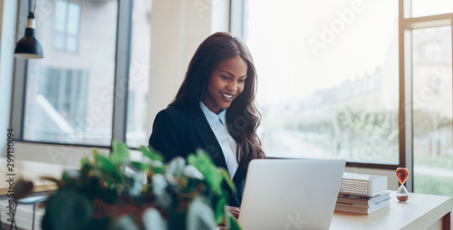 Foto op Canvas Wild West Smiling African American businesswoman using a laptop at her des