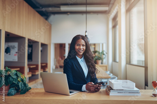 Pinturas sobre lienzo  Smiling African American businesswoman working alone in an offic