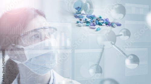 Fotografia  woman scientist looking at pills behind a grey screen