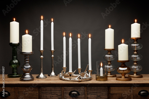 Obraz na plátně A group of candle sticks and glowing candles, shot on a wooden table, with a dar