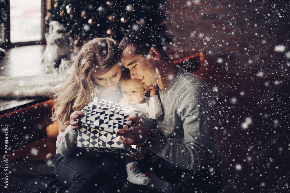 Fototapety, obrazy: Full length portrait of cheerful loving parents and their baby girl sitting on the floor surrounded by wrapped Christmas gifts. Daughter playing with bowl of Christmas balls.