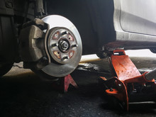 Remove The Wheel For Cleaning Or Maintenance The Wheels. Nut Screwing A Car Hub. Jack For Lifting The Vehicle.