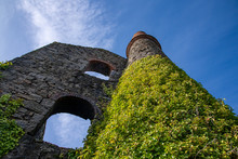 A Dramatic Image Looking Up At The Ivy Covered Chimney And Engine House Of An Abandoned Tin Mine In Cornwall