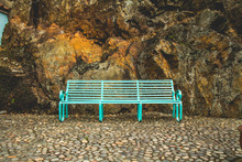 Turquoise Metal Bench In Front Of Natural Orange Cliff Side Rock