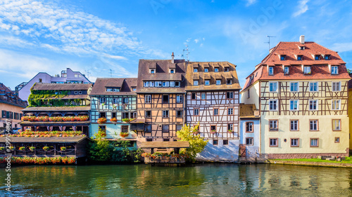 Photo Panoramic front view of typical half-timbered buildings with pastel facades lining the river Ill in the Petite France quarter in Strasbourg, France, on a sunny morning
