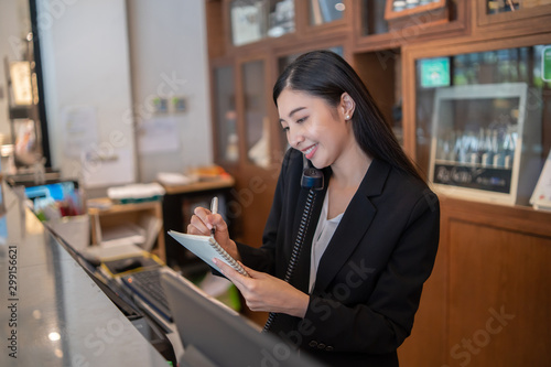 Welcome to the hotel,Happy young Asian woman hotel receptionist worker smiling s Fototapet