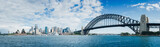 A large panorama of Habour Bay with views of city of Sydney, Opera House and Habour Bridge on a blue sky. With white clouds