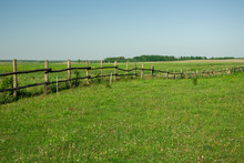 Wooden Fence On A Green Meadow And Blue Sky