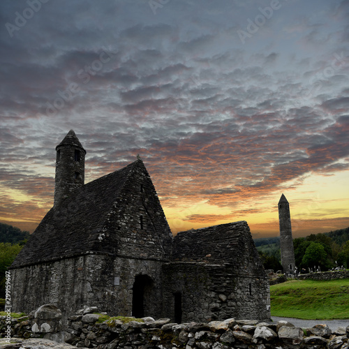 Fototapeta view to the ruins of monastic cemetery of Glendalough, Ireland while sunset , an