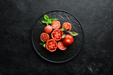 Tomatoes In A Plate On A Black Stone Background. Vegetables. Top View. Free Space For Your Text.