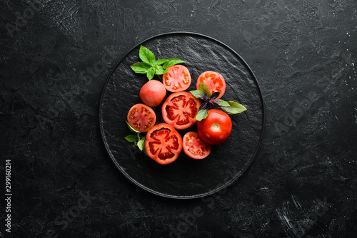 Fotomural  Tomatoes in a plate on a black stone background