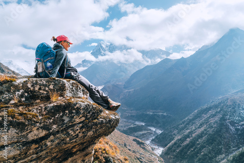 Foto auf AluDibond Logo Young hiker backpacker female sitting on cliff edge and enjoying the Imja Khola valley during high altitude Everest Base Camp (EBC) trekking route near Phortse, Nepal. Active vacations concept image.