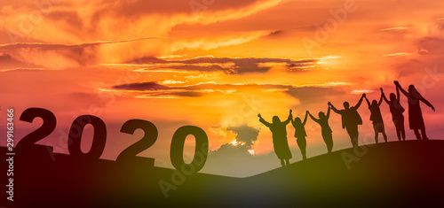fototapeta na ścianę Happy new year 2020, Silhouette of 2020 letters on the mountain with business people raised arms in teamwork concept at sunrise.