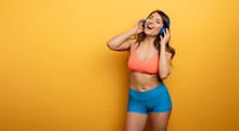 Fitness Girl Listens To Music With Headset. Joyful And Happy Expression On Yellow Background
