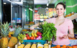 Portrait of young satisfied female purchaser holding shopping basket with fruits and vegetables