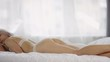 Panning medium shot of young blonde Caucasian woman in lacy bra and tanga panties lying on stomach on bed in morning and sleeping