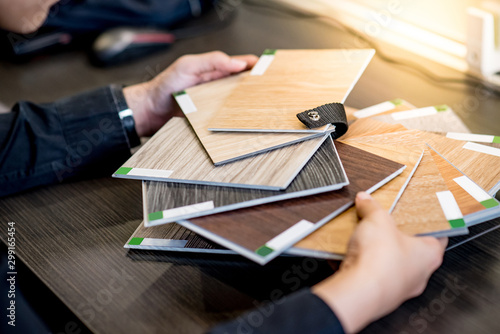 Fotomural  Male architect or interior designer holding wooden color swatch choosing wood material for housing project