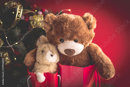 mata magnetyczna Christmas card with Teddy and bunny in red gift bags under the Christmas tree. With holiday decoration and presents