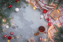 Christmas Tea Cup With Cinnamon, Cookies, Fir Tree Branches, Toys, Presents, Plaid On Concrete Linen Background