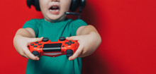 Small Boy In Headphones And Joystick On Red Background