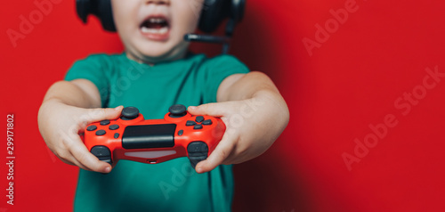 small boy in headphones and joystick on red background Wallpaper Mural