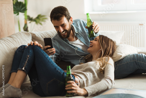 Young couple enjoying in MP3 music while drinking beer at home Fototapeta