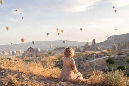 Montage in der Fensternische Cappuccino woman is watching on scenery view with rising balloons on sunrise. Girl in gorgeous pink long dress sit on hill looking at large number of air balls. Fabulous Cappadocia mountains landscapes Turkey