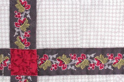 Fabric patchwork from colored fabrics with handmade folk ornament as a background, place for text.