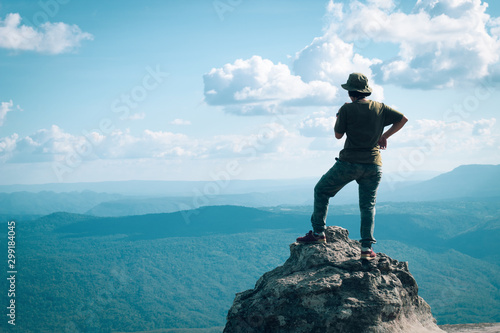 teen girl standing on nature cliff with forest lanscape background, adventure trip tourism, holiday vacation with backpack travel to moutain