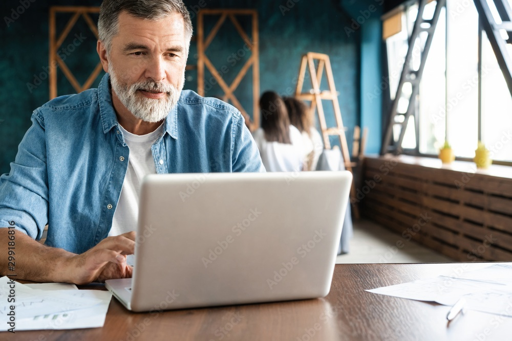 Fototapeta Cheerful mature man working on laptop and smiling while sitting at his working place