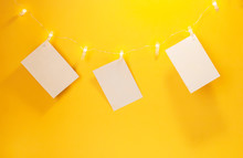 Clothespin Photo. Luminous Garland With A Place For Photography On A Yellow Background. Holiday.