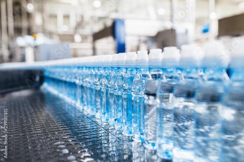 Fényképezés  Bottling plant - Water bottling line for processing and bottling pure spring water into blue bottles