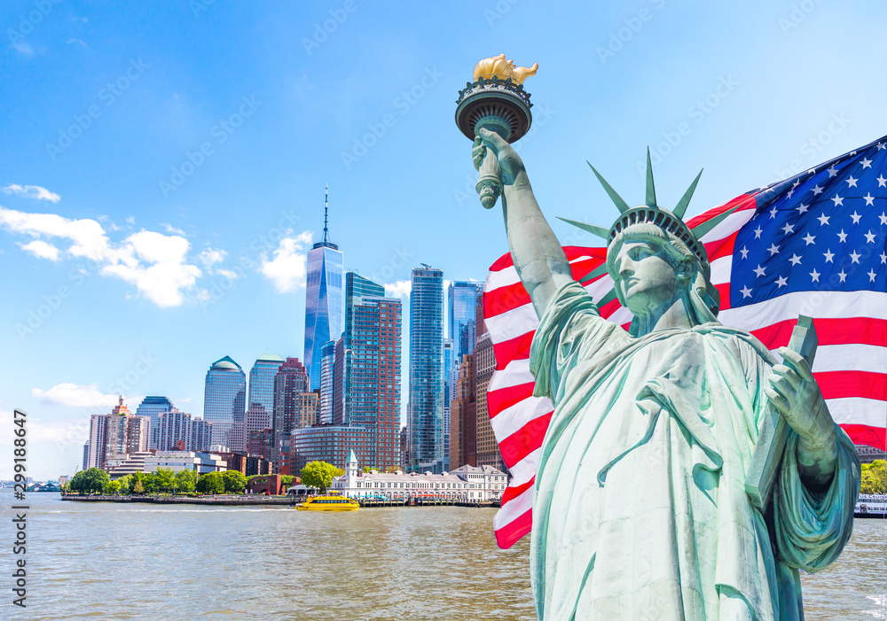 Fototapety, obrazy: Statue of Liberty with a large american flag and New York skyline in the background