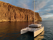 Moored Lonely Modern Catamaran In Calm Waters Of Atlantic Ocean Near Rocky Volcanic Cliff. Tenerife, Canary Islands, Spain. Concept Of Lifestyle, Adventure Activity, Beautiful Nature And Freedom