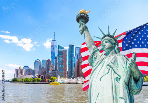 Statue of Liberty with a large american flag and New York skyline in the background - 299188647
