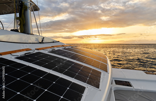 Photo Solar powered catamaran at sunset, fully sustainable and powered by solar energy, charging batteries aboard a sailboat, vessel in ocean waters, nobody
