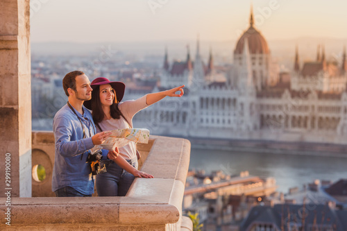 Young couple searching right direction on map from the point from Fisherman Bastion in Budapest with Hungarian Parliament building on background