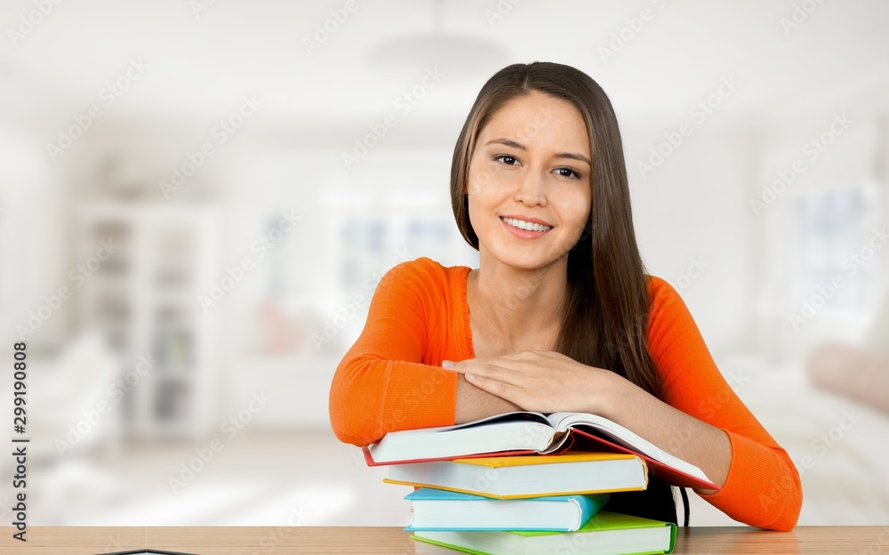 Fototapeta Young female college student and stack book on table at library background